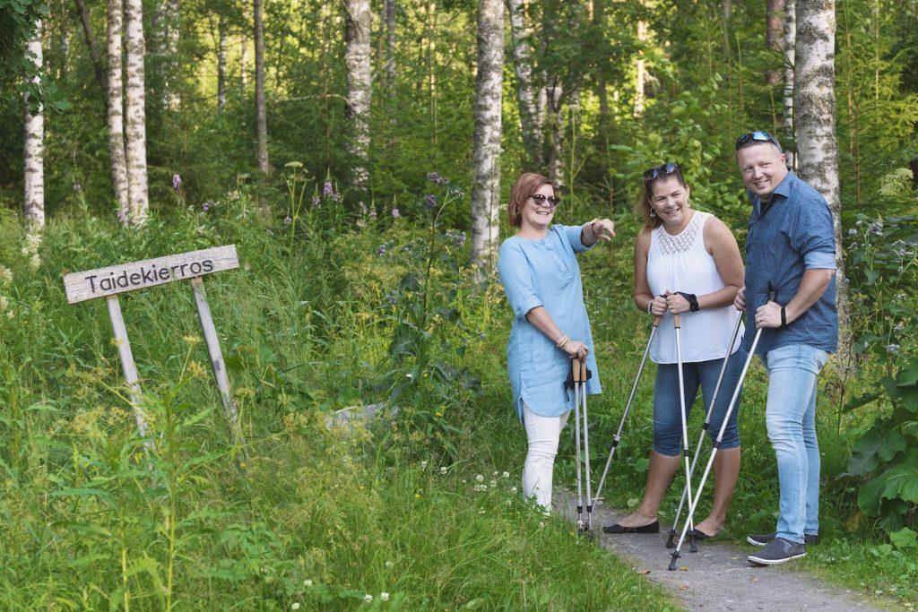 Ystävykset ryhmille suunnatulla luonto-opastuksella kävelysauvat kädessään.