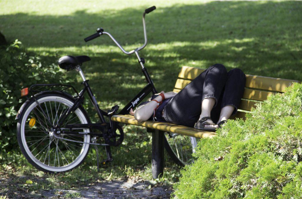 Eine Frau ruht sich aus am Bank im Park des Serlachius Museums Gösta.