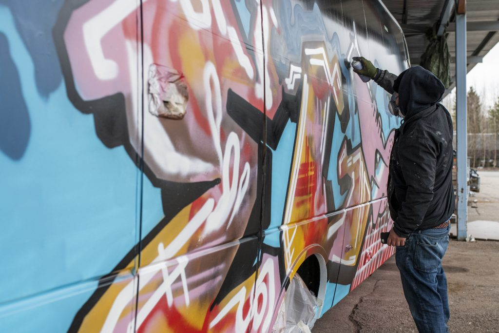 Graffititaiteilija EGS maalaa Serlachius-bussia.